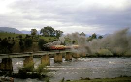 Steam train with passenger carriages crossing Derwent River