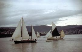 Yachts on river, one with black sail