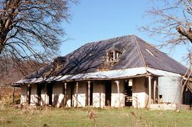 Front view of abandoned shingle-roofed dwelling on Montacute property