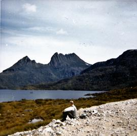 Man sitting on gravel near Cradle Mountain