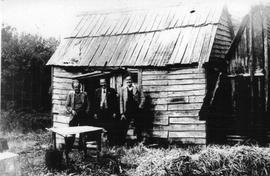 View of three men standing outside a rough hewn timber building in the bush. Macquarie Harbour, Tasmania