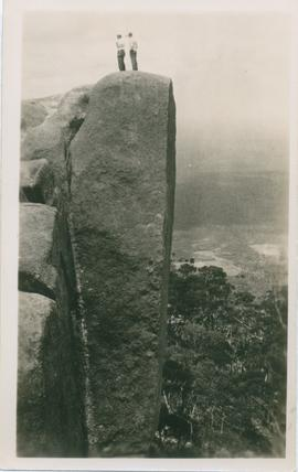 Photograph of two people on rock