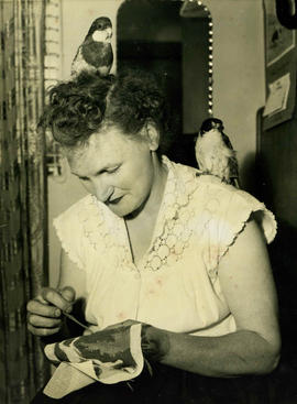 Marjorie with her pet birds and her needlework